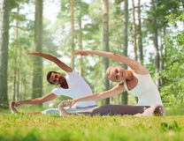 Happy couple stretching and doing yoga exercises Stock Photography