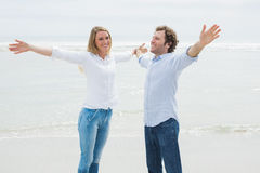 Happy couple stretching hands out at beach Royalty Free Stock Photos