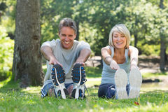 Happy couple stretching in park Stock Photo