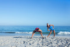 Happy couple stretching together beside the water Royalty Free Stock Photography