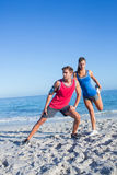 Happy couple stretching together beside the water Stock Photo