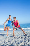 Happy couple stretching together beside the water Royalty Free Stock Images