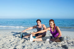 Happy couple stretching together beside the water Royalty Free Stock Photo