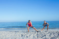 Happy couple stretching together beside the water Stock Photos