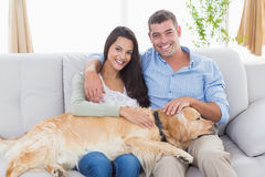Happy couple stroking dog while sitting on sofa Stock Image