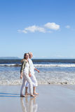 Happy couple strolling barefoot on the beach Stock Images