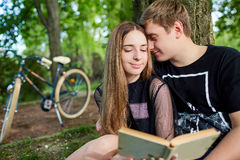Happy couple of students are reading a book in the park royalty free stock photos
