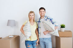 Happy couple with stuff moving to new home Royalty Free Stock Photography