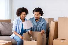 Happy couple with stuff moving to new home Royalty Free Stock Photos