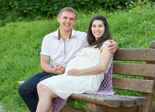 Happy couple in summer city park outdoor, pregnant woman, bright sunny day and green grass, beautiful people portrait Stock Image