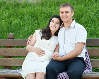 Happy couple in summer city park outdoor, pregnant woman, bright sunny day and green grass, beautiful people portrait Stock Images