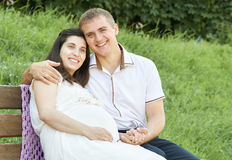 Happy couple in summer city park outdoor, pregnant woman, bright sunny day and green grass, beautiful people portrait, yellow tone Stock Photography