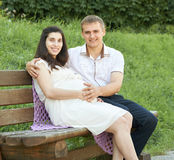 Happy couple in summer city park outdoor, pregnant woman, bright sunny day and green grass, beautiful people portrait, yellow tone Stock Image