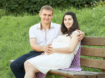 Happy couple in summer city park outdoor, pregnant woman, bright sunny day and green grass, beautiful people portrait, yellow tone Stock Images