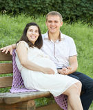 Happy couple in summer city park outdoor, pregnant woman, bright sunny day and green grass, beautiful people portrait, yellow tone. D stock photography