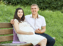 Happy couple in summer city park outdoor, pregnant woman, bright sunny day and green grass, beautiful people portrait, yellow tone Royalty Free Stock Photos