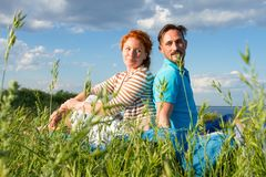 Happy couple in summer grass on sky background. Together man and woman sitting in field royalty free stock photo