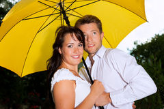 Happy couple in the summer rain with umbrella Stock Photography