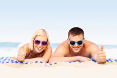 Happy couple sunbathing at the beach Stock Photos