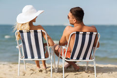 Happy couple sunbathing in chairs on summer beach Stock Images