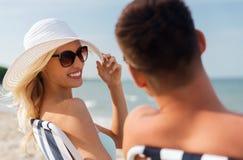 Happy couple sunbathing on summer beach Stock Photos