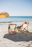 Happy couple sunbathing on their deck chairs Stock Photo