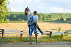 Happy couple with sunflowers having fun and walking along country road outdoors, girl riding on his back - romantic travel, hiking Royalty Free Stock Photo