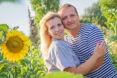 Happy couple among sunflowers Stock Photo