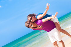 Happy couple in sunglasses on holiday piggybacking Royalty Free Stock Photography
