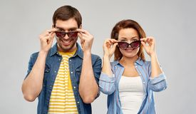 Happy couple in sunglasses over grey background. Summer, eyewear and people concept - happy couple in sunglasses over grey background stock image