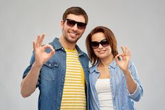 Happy couple in sunglasses showing ok hand sign. Summer, eyewear and people concept - happy couple in sunglasses showing ok hand sign over grey background royalty free stock image