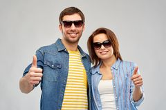 Happy couple in sunglasses showing thumbs up. Summer, eyewear and people concept - happy couple in sunglasses showing thumbs up over grey background royalty free stock image