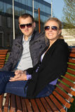 Happy couple in sunglasses sitting on the bench Royalty Free Stock Photography