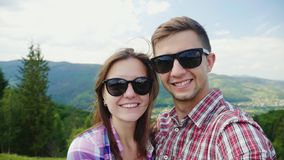 A happy couple in sunglasses takes pictures of themselves in a picturesque place on the background of the mountains royalty free stock images