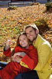 Happy Couple in sunny Autumn Park. Fall. Young Family Having Fun Outdoors. Yellow Trees and Leaves. Laughing Man and Woman outside Stock Photo