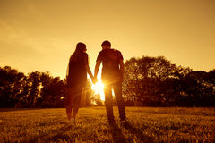 Happy couple at sunset in park view from behind.  Royalty Free Stock Image