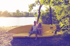 Happy couple of sup surfers is relaxing in a river camping. Looks at the sun, uses sup like sofa Royalty Free Stock Images