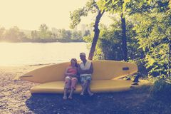 Happy couple of sup surfers is relaxing in a river camping. Looks at the sun, uses sup like sofa Stock Images