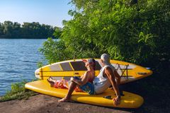 Happy couple of sup surfers is relaxing in a river camping. Looks at the sun, uses sup like sofa Stock Photos