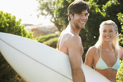 Happy Couple With Surfboard At Beach. Portrait of young men carrying surfboard with girlfriend in bikini at beach Royalty Free Stock Images