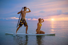 Happy couple surfing together on paddle board at sunset stock photo