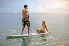 Happy couple surfing together on paddle board at sunset Royalty Free Stock Photo
