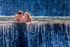 Happy couple swimming in natural spring waterfall pool Royalty Free Stock Images