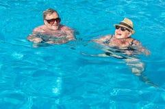 Happy couple in swimming pool. Happy couple of seniors enjoying in swimming pool Stock Image