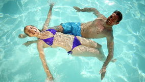 Happy couple swimming in a pool stock footage