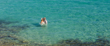 Top view of happy couple swims after wedding in turquoise sea. Romantic newly-married couple enjoying a summer vacation. Stock Photography