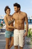 Happy couple in swimsuit at holiday beach resort. Happy caucasian couple in swimsuit at summer beach holiday resort. Smiling, looking at camera. Handsome men and Stock Photo