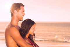 Happy couple in swimsuit hugging while looking at the water Stock Images