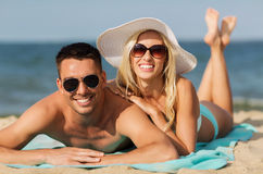 Happy couple in swimwear lying on summer beach Stock Image