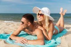 Happy couple in swimwear lying on summer beach Royalty Free Stock Image